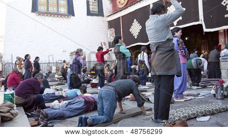 LHASA, TIBET - OCTOBER 07: Tibetan Buddhist pilgrims pray in front of the holy Jokhang Monastery on October 07, 2012 in Lhasa, Tibet.