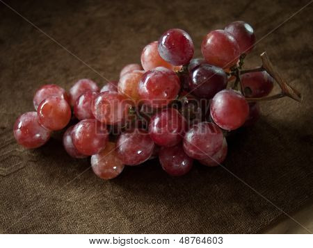 Red Grapes On Brown Cloth