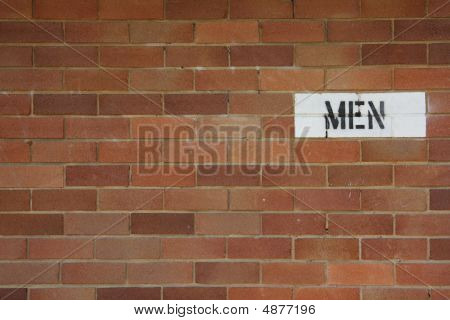 Men Sign On Brick Wall For Public Restroom
