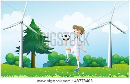 Illustration of a boy playing football near the windmills
