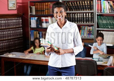 Portrait of happy female librarian holding books while standing in library with students studying in background