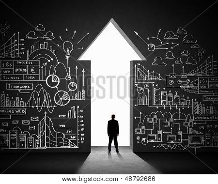 Silhouette of businessman against black wall. Business direction