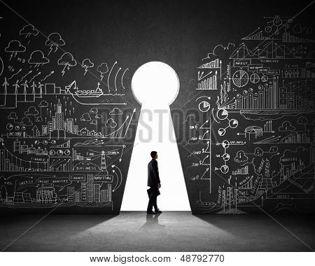 Silhouette of businessman against black wall with key hole