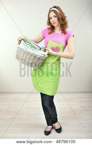 Housewife carrying laundry basket full of clothing in room on grey background
