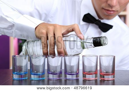Bartender is pouring  vodka into glasses