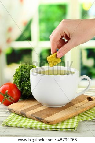 Cup of soup with bouillon cube on wooden table