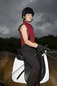 picture of riding-crop  - Side view portrait of a female horseback rider sitting on brown horse - JPG