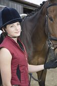 picture of riding-crop  - Portrait of a young woman in riding hat with a horse outdoors - JPG