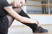 stock photo of leg warmer  - Beautiful young woman resting in ballet rehearsal room - JPG