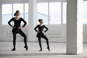 picture of ballerina  - Full length of ballerina teaching young girl in empty warehouse - JPG