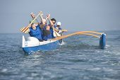 stock photo of canoe boat man  - Multiethnic outrigger canoeing team in race - JPG