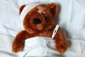 stock photo of teddy-bear  - sick teddy bear with injury in a bed in the hospital - JPG