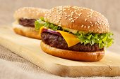stock photo of burger  - Homemade grilled gourmet hamburgers on wooden board