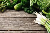 stock photo of abundance  - Frame with green organic vegetables on wooden background - JPG