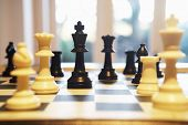 stock photo of indoor games  - Chess pieces standing on chess board - JPG