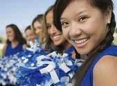 image of pom poms  - Blurred cheerleaders in a row with focus on girl in foreground - JPG