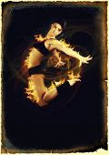 stock photo of zumba  - Jumping woman on black background in flames