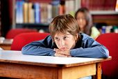 Bored little schoolboy looking away while leaning on table in library with female classmate in backg