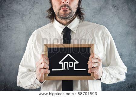Businessman Holding Blackboard House Drawing