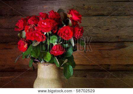 Beautiful Roses With Frech And Wilted Buds In Ceramic Jug On Rustic Wooden  Background