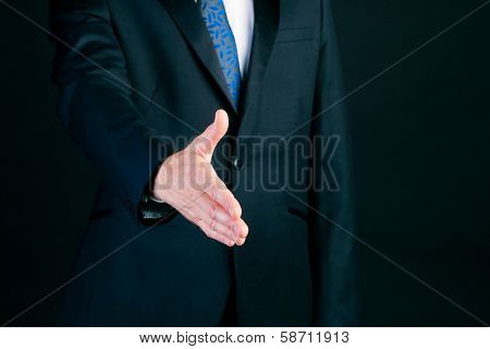 Business man or manager in suit offering handshake in front of black background
