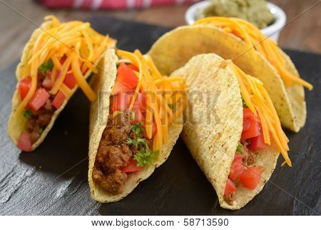 Tacos with ground beef, cheese, vegetables and guacamole sauce.