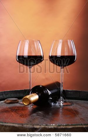 Red wine and bottle on a barrel top