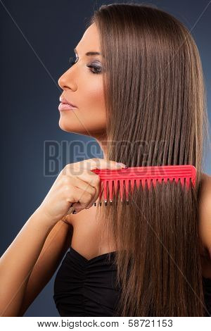 Beautiful Young Woman Combs Her Hair