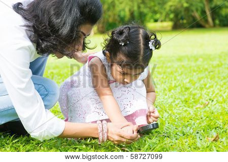 Cute Indian girl peeking through magnifying glass with parent on green lawn. Mother and daughter exploring nature at outdoor garden.
