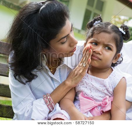 Indian family outdoor. Parent is comforting her crying child.
