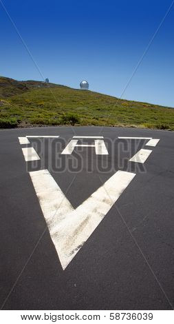 LA PALMA, CANARY ISLANDS, SPAIN - JULY 14, 2012: Heliport H triangle sign at ORM observatory at Roque de los Muchachos by IAC institute,GTC at background in La Palma, Canary, Spain, July 14, 2012.