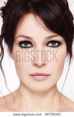 Close-up portrait of beautiful mature woman with smoky eyes and messy hairdo
