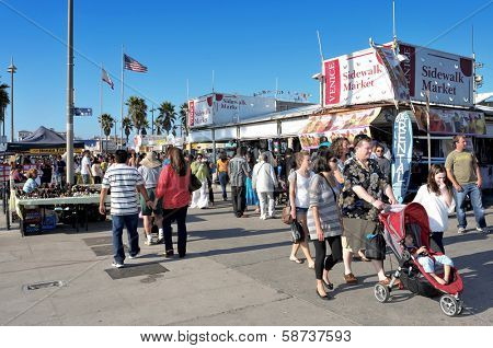VENICE, CA -  OCTOBER 17: Crowd in Ocean Front Walk of Venice Beach on October 17, 2011 in Venice, US. This boardwalk is 2.5 kilometer long and is full of stores and stalls