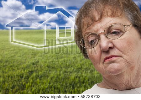 Melancholy Senior Woman with Green Grass Field and Ghosted House Behind Her.