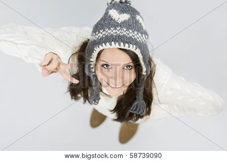Pretty young woman in warm winter woollen pullover and grey cap, looking up and smiling while making victory sign, isolated on grey background.