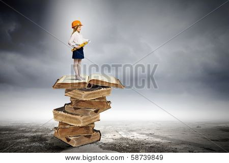 Image of cute school girl in hardhat standing on pile of books