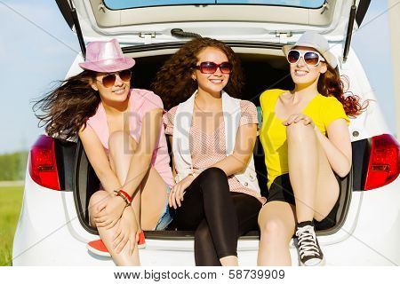 Three young pretty lady sitting in car boot
