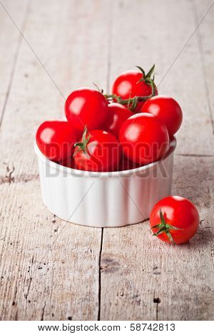 ripe tomatoes in bowl on wooden background