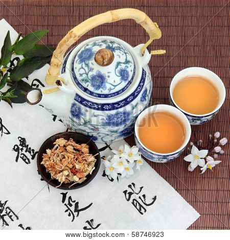 Jasmine flower tea with oriental style teapot, cups and spoon and chinese calligraphy. Su xin hua.