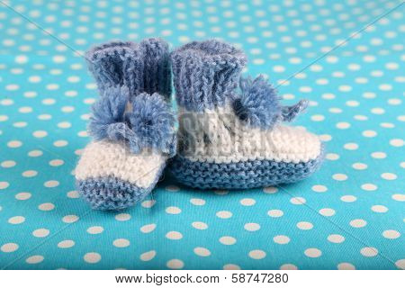 Crocheted booties for baby, on color background