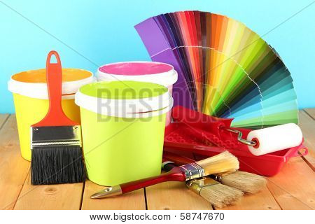 Paint pots, paintbrushes and coloured swatches on wooden table on blue background