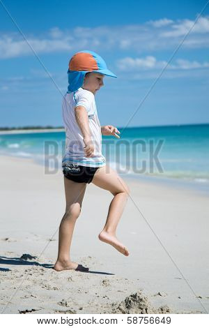 Young boy is acting like a lifesaver on a white sand beach