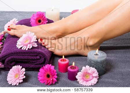 Bare Feet Of A Woman Surrounded By Flowers