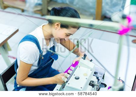 Asian Seamstress or worker in a Indonesian factory sewing with a industrial sewing machine, she is very accurate