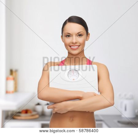 diet and sport concept - beautiful sporty woman with scale in kitchen