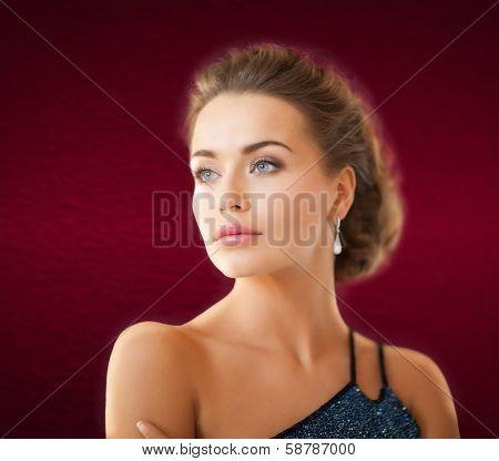 jewelry and beauty concept - beautiful woman in evening dress wearing diamond earrings