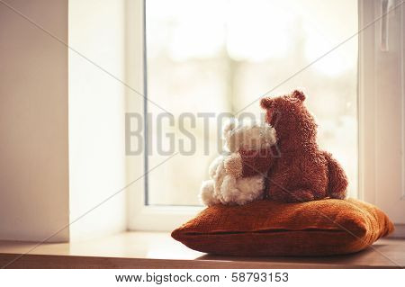 Two Embracing Teddy Bear Toys Sitting On Window-sill