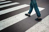 stock photo of zebra crossing  - Legs of young woman in jeans and leather boots crossing street on zebra marking - JPG
