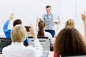 stock photo of business class  - Young teacher in classroom standing in front of class - JPG