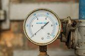picture of air pressure gauge  - Rusty Pressure Gauge connected to pipes with brick wall behind - JPG